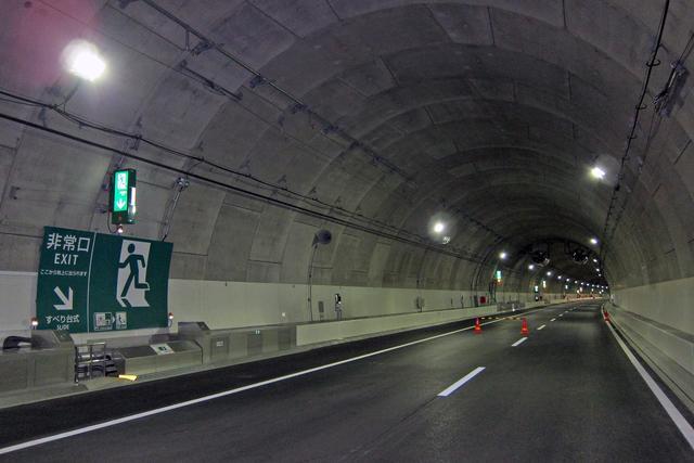 画像: シールド工法で造られたトンネルの内部。路面幅は9.75m。写真左側の非常口がすべり台方式のもの。