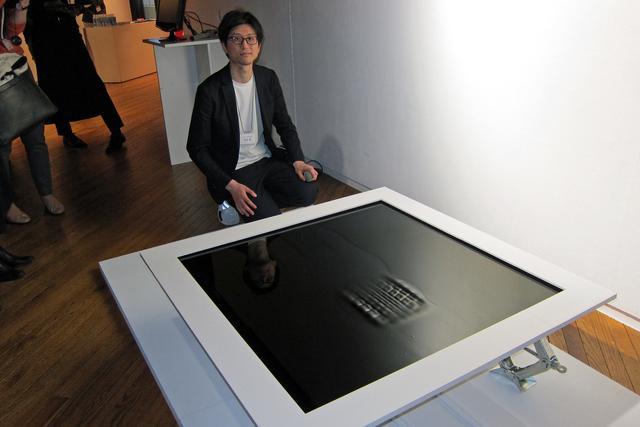 画像: 発表会場に展示された小型の模型と吉泉デザイナー。盤面上に磁性流体技術で浮き出たタイヤのパターンが、クルマがとおりすぎるようなタイヤの軌跡を動いて見せる。