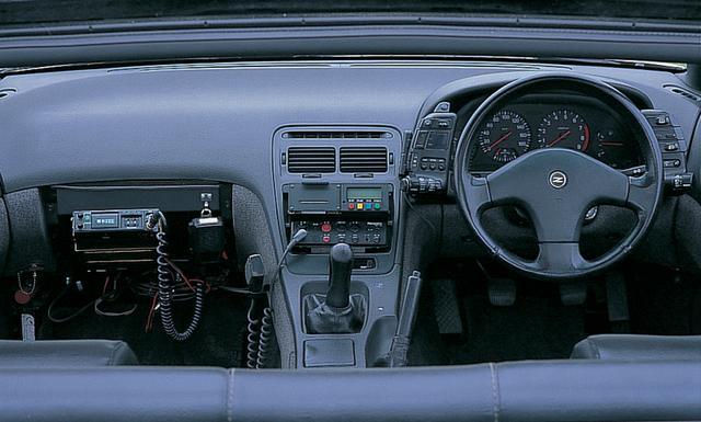 画像: オーディオが入るスペースには、ストップメーターとサイレンアンプを装着。1992年式ゆえエアバッグはまだオプション設定だったので付いていない。ただでさえタイトな助手席の膝先には無線機器が装着されていた。