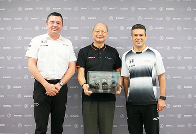 画像: 2016年の「10周年」イベントでは、タッグを組んだ2007年の第1戦で初めて表彰台を獲得した時のステアリングホイールが、曙ブレーキ工業 社長 信元久隆氏(写真中央)に贈呈された。左は、マクラーレンチームのレーシングダイレクター エリック・ブーリエ氏で、右が同コマーシャル&フィナンシャルダイレクター ジョン・クーパー氏。