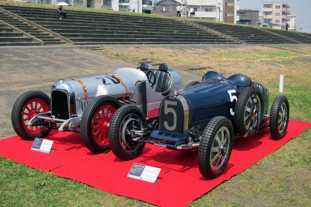 画像: 2016年5月、プレート設置記念式典に展示された、本田宗一郎氏の駆った1924年式カーチス号(左)と1926年式ブガッティT35C。どちらも80年前に出走した実車だ。奥に見えるのがコンクリート製の観客席跡。