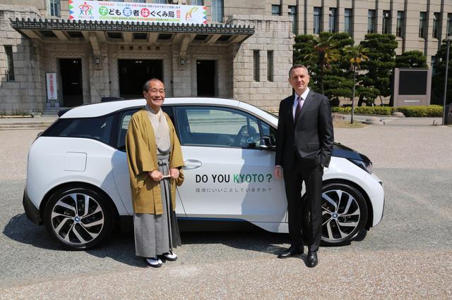 画像: 京都市庁舎前で実施された4月4日の車両引き渡し式では、BMWのクロンシュナーブル社長(右)から門川市長にBMW i3が直接手渡された。