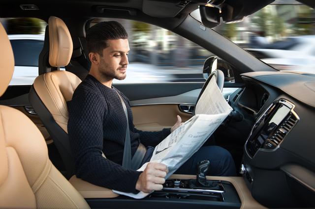 画像: 自動運転レベル3では、走行中にステアリングから手を離して新聞や雑誌を読んでもOKになる