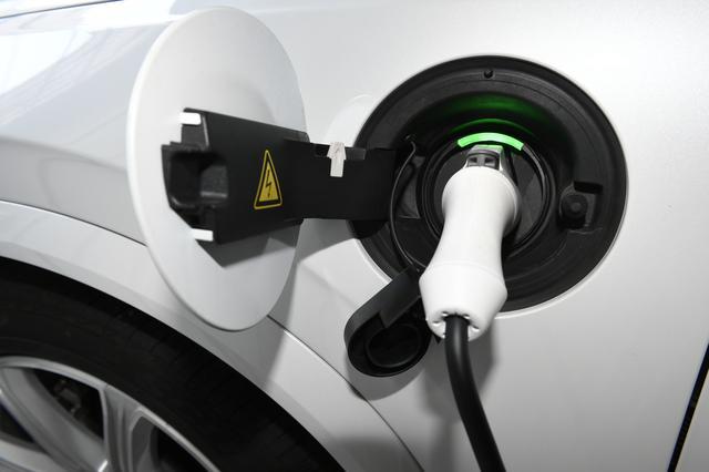 画像: 付属のケーブルで充電。クルマをロックするとケーブルも抜けないように固定される。充電の状況は充電口の色によりわかる。