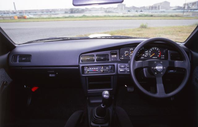 画像: 写真はNISMOオプションの3本スポークステアリングを装着した状態。ノーマルでは、ステアリングは商用車のような2本スポークのPPステアリング、内装も快適装備はほとんど外されて軽量化が図られていた。