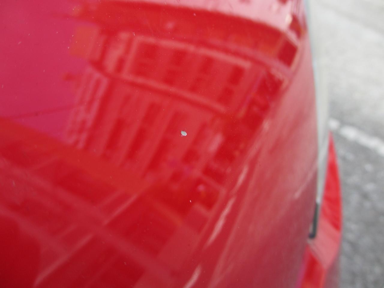 画像: MMアップ!号の洗車と掃除をしていて気が付いた、跳ね石によるボンネットのキズ(その1)。左ヘッドライト上方あたりで塗装が剝がれている。けっこう大きめの石が当たった感じだが、目立つほど凹んではいないのが幸いである。