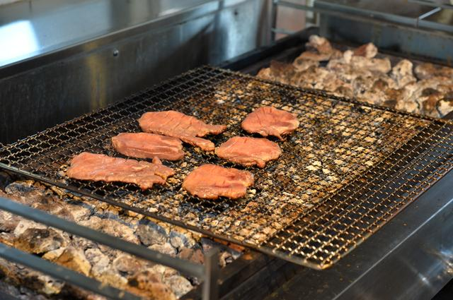 画像: 熱した熔岩石の熱で肉を焼く。遠赤外線効果もあり、調理スペース全体が蒸し風呂のような暑さだ。