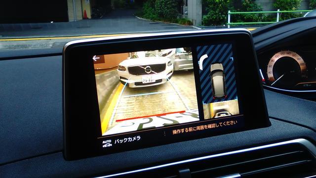 画像: バックで縦列に駐車。カメラの視界は広めで、背後の車両とともに周囲を確認することができる