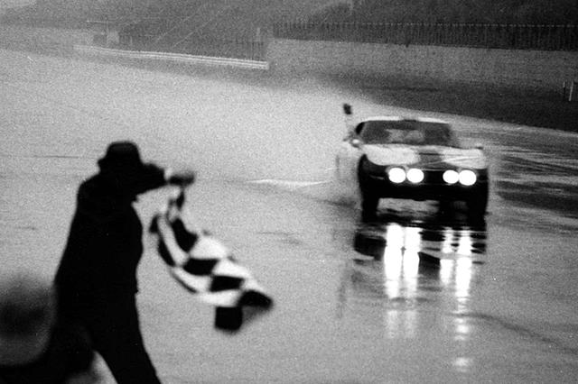 画像: 1967年の富士1000kmゴールシーン、雨中でチェッカーを受ける細谷四方洋/大坪善男組のトヨタ2000GT。