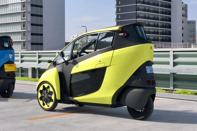 画像: i-ロードは「ミニカー」や「マイクロカー」に分類され、50cc以下の原動機付き3輪車(1人乗り)として青ナンバー登録となる。2人乗りの場合は画像左のように軽自動車の黄色ナンバーとなる。