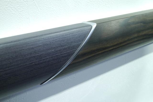 画像: こちらは CX-8 に使われている本杢パネル(左側)と自然の木目の比較展示。本杢パネルのシャープな直線基調の木目は、薄い板を重ねてからカットするという手間をかけることで実現した。