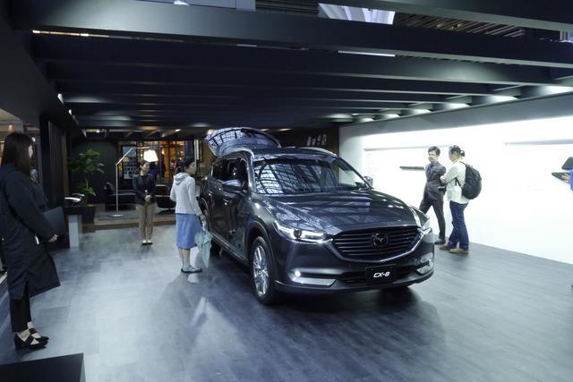 画像: スタンドは部屋とガレージを一体化したような作りで「上質さと落ち着きに満ちた空間」を表現。CX-8 の奥には・・・