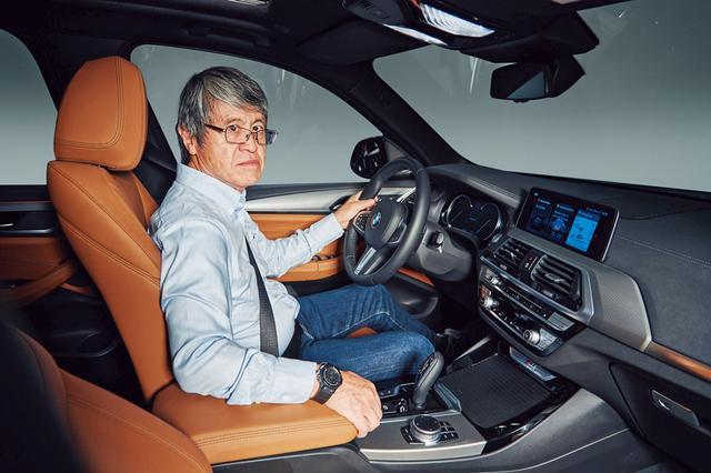 画像: ニューX3の運転席に座り、現行型と比べてその質感の向上ぶりに驚く木村レポーター。