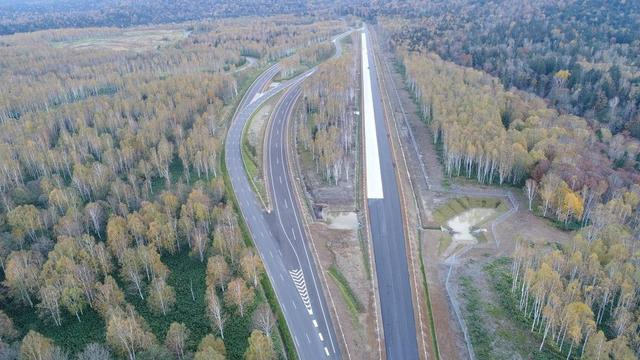 画像: 高速周回路の一部。左側が高速道路の緩やかなカーブ。右側直線の白い部分がコンクリート舗装路。