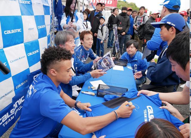 画像: 写真は5月のスーパーGT富士ラウンドのサイン会の模様。ドライバーも揃ってのサイン会に大盛況でした。