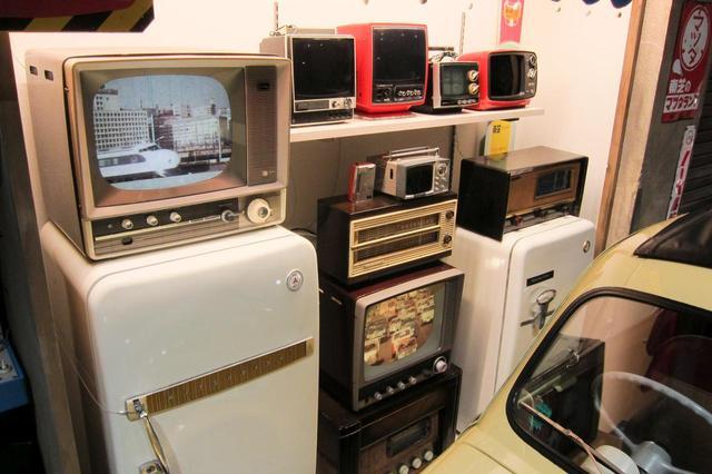 画像: ラジオ、白黒テレビ、冷蔵庫など1960年代当時の電気製品が並ぶ。