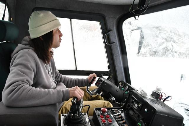 画像: 雪上車ワイルドモンスター号を操るオペレーターの茶原さん。両手両足を駆使して操縦、雪原を駆け上っていく。