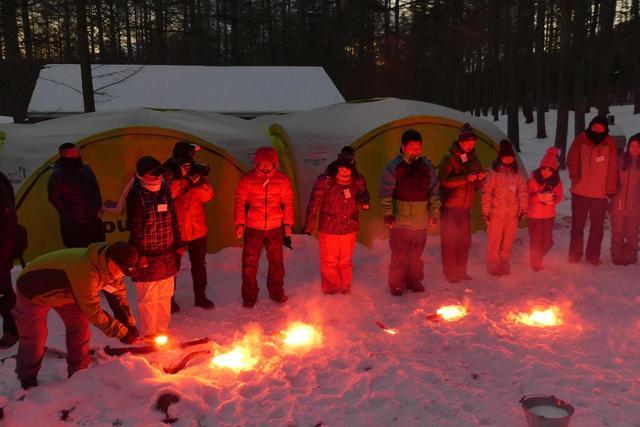 画像: みんなで発炎筒の点灯方法を学ぶ。雪の上に置いても火は消えないのだ。