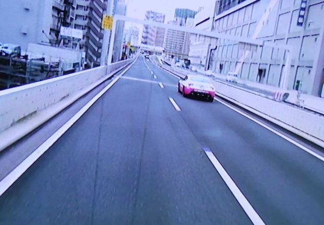 画像: 「首都高」を守るホメパト(トヨタ86)による、正しい追い越しのデモンストレーションも行われました(画像はバス車内のモニター)。