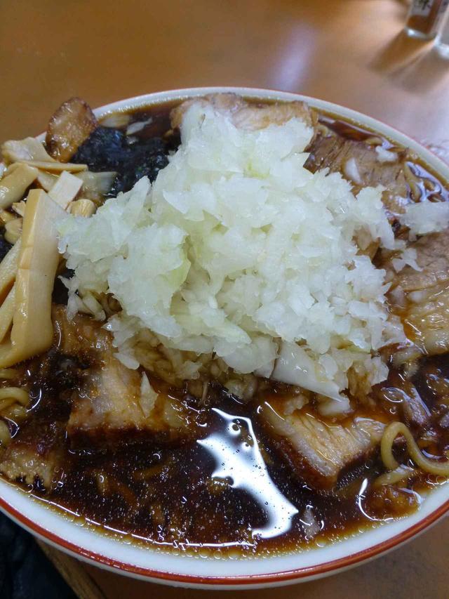 画像: 溢れんばかりの黒いスープ(てか、本当に溢れてテーブルにスープがこぼれている)が特徴。チャーシューメンは肉が8枚、ふつうのラーメンは4枚入っている。