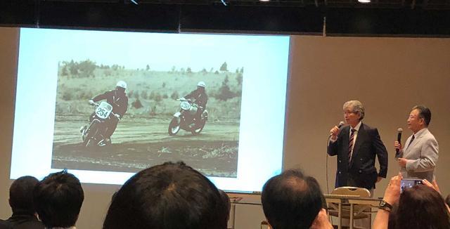 画像: 現在チームクニミツの総監督を務める高橋国光氏(右)。左は自動車評論家の山口京一氏。氏は、高橋氏が二輪のレーサーになるきっかけを作った人物だ。
