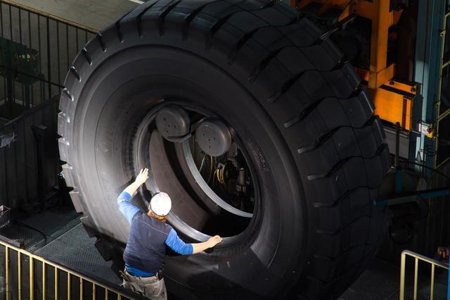 画像: 鉱山で稼働するダンプカー用の大型タイヤの生産は熟練作業員の手が必要になる。