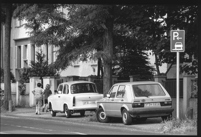 画像: 「2000年、ドイツのオフェンバッハ。路肩に駐車している2台のクルマを脇を子供たちが通り過ぎていく。見ればこのクルマ、旧東ドイツのトラバント、旧西ドイツの初代ゴルフだった」(永元)