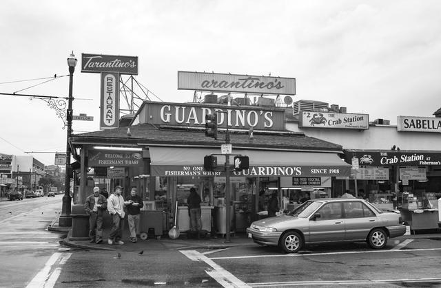 """画像: 「2003年、サンフランシスコ。フィッシャーマンズワーフのレストランはだれをも幸せに満たしてくれそうだった。人もクルマもハトも。今も変わらず営業しているだろうか。店のひさしには""""SINCE 1908""""とあるから今では創業110年になる」(永元)"""
