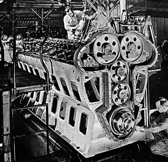 画像: 組立中でまだシリンダーブロックだけだが、それでも人と比べるとデカイ! この上部にカムカバー、吸排気配管とラジエターが、前方に機械式過給器と発電ユニットが、ドッカリ装着される。