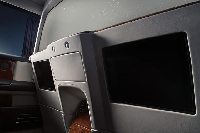 画像: 前後席の仕切りガラスの下に配置されたモニターと開口部。