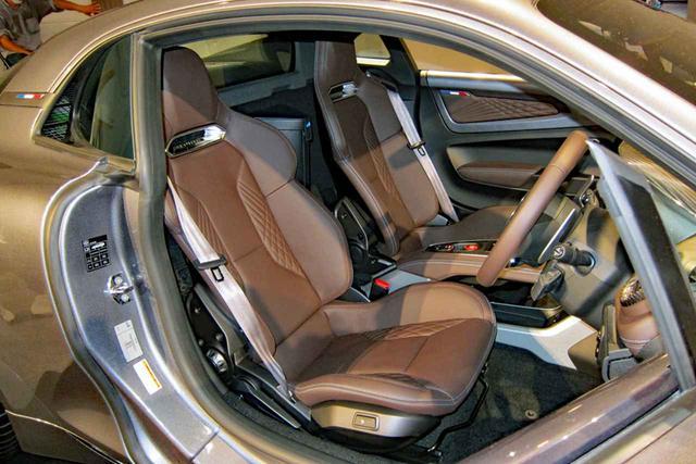 画像: リネージのシート地はブラウンレザーでヒーターも内蔵。助手席の後ろにサブウーファーが備わる。
