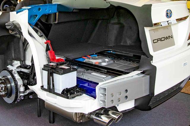 画像: 新型クラウンに設定されているハイブリッドカーのカットモデル。補機用バッテリーと駆動用バッテリーは、両方ともトランクスペースの下に格納されている。
