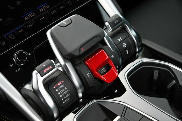 画像: 中央の赤いカバーの下に設けられたスタート/ストップボタン。その上にあるレバーを手前に引くとリバースに入る。左側のレバーでドライブモードを選択する。