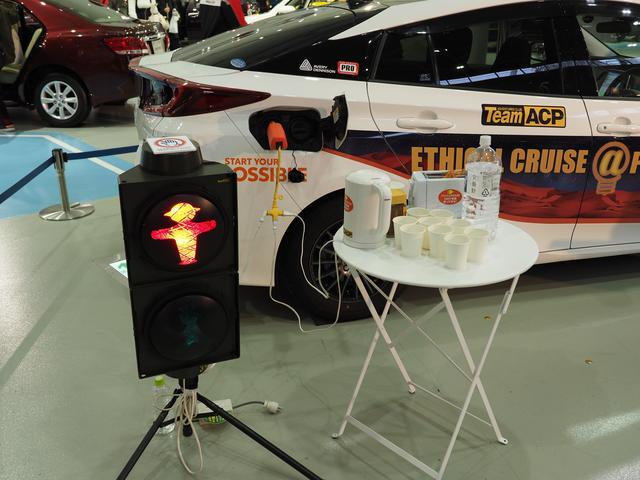 画像: プリウスPHVによる給電デモンストレーションを実施。手前の信号機はドイツ製で携帯用。