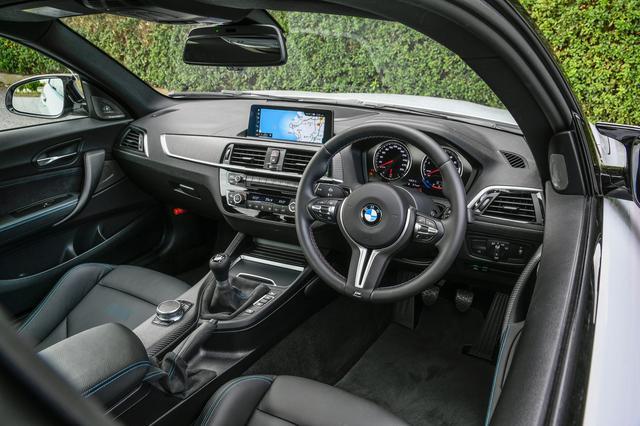画像: M2コンペティションのMスポーツステアリングには、走行モードをプリセットできるM1、M2スイッチが装備されている。