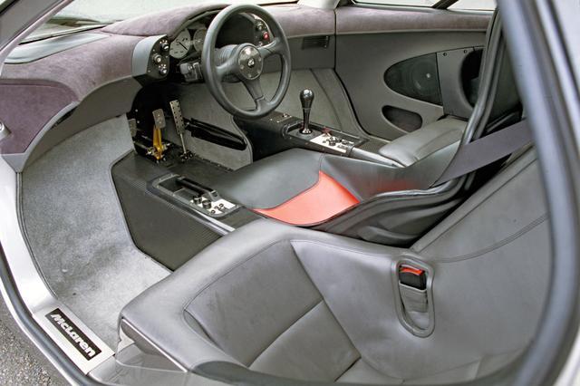 画像: 運転席右にシフトノブとエアコンのスイッチ類、左にパーキングブレーキとオーディオのスイッチ類が備わる。