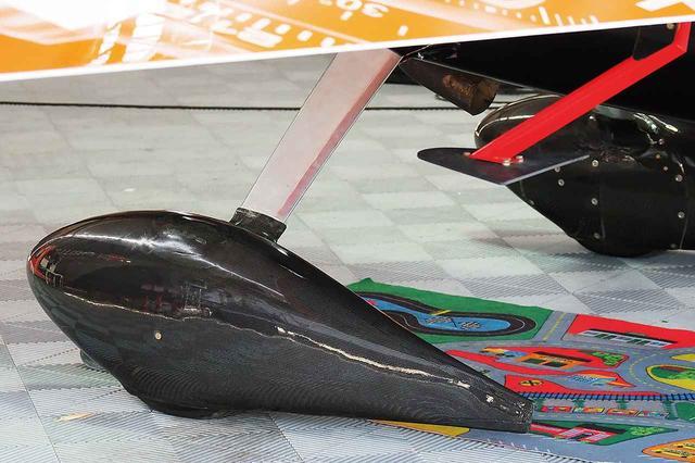 画像: 主脚のカバー。カーボン製でどのチームもエアロデザインに特徴がある。補助翼から突き出ている赤いステーの先端にスペードと呼ばれるフィンが装着されている。