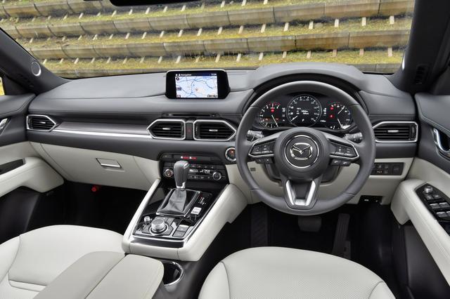 画像: CXー8のインパネ。内装色はピュア・ホワイト。商品改良時に前席中央のアームレストが約15mm低くされてしっくりくるように。荷室はフル乗車しても十分なスペースが残り、最大にするとご覧のとおり広大でフラットになる。