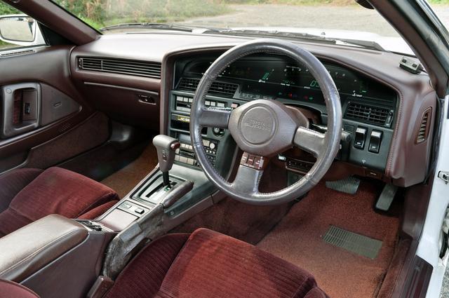 画像: 前期型の内装色はバーガンディ。ステアリングスポークにはオートドライブのスイッチが備わる。