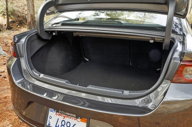 画像: セダンのトランクの開口部は少し高め。荷室側からシートバックを倒すレバーが設置されている。