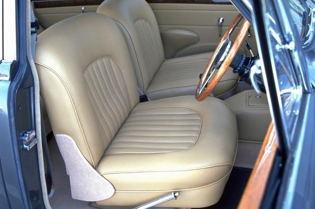 画像: ビスケットと呼ばれる明るいベージュのシートやドアトリムは、コノリーレザー製。運転席右にパーキングブレーキのレバーがある。