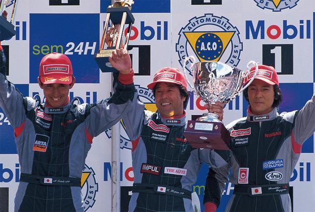 画像: 満面の笑みでル・マンの表彰台に立つ星野。R390GT1の熟成とチーム体制の強化により、星野にとって最後のル・マン挑戦となるこの年、亜久里と影山のトリオで3位表彰台に登った(1998年6月7日-8日、ル・マン24H)。