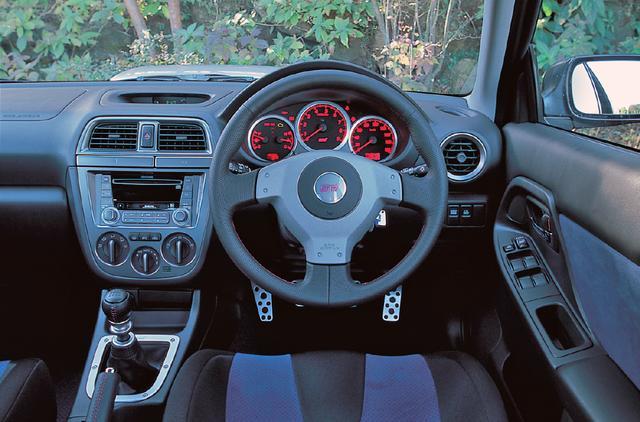 画像: STiはスポーツ走行に最適な375mmφの小径ステアリングを採用。レッドルミネセントメーターも採用された。