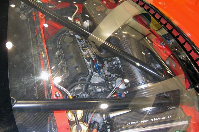 画像: ポリカーボネート製のリアウインドー越しに横置きされたV6エンジンが見える。