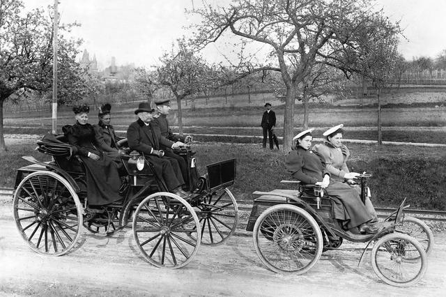 画像: 後ろの大きなクルマがベンツ・ビクトリア。それに比べると前を走るヴェロの小ささがわかる。ヴェロに乗る2人は、カール・ベンツの娘たち。