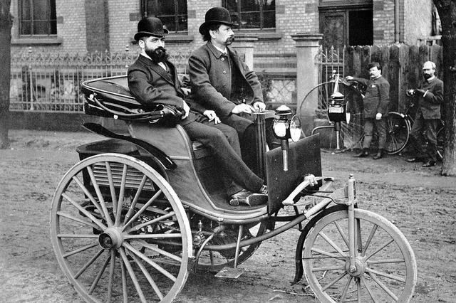 画像: ベンツ1号車の改良版。車輪が木製になっている。ハンドルを握っているのは、ベンツ社の創始者カール・ベンツだ。後方では自転車の傍で見物する人物が見える。