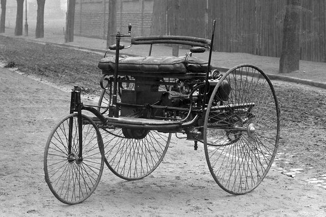 画像: 1885年から86年にかけて開発された、歴史的なベンツ1号車。自転車そのものの細いワイヤーホイールやパイプ式フレームが目立つ。床下にエンジンを積んでいる。