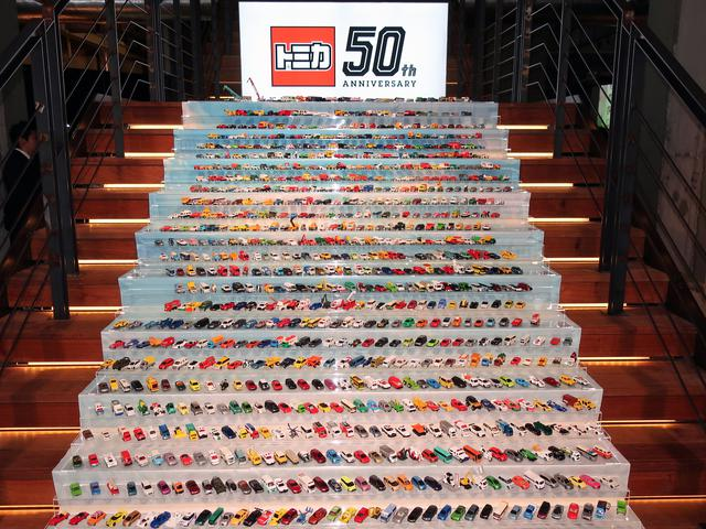 画像: 会場入口に、ズラリと並べられた約1000台あまりのトミカ。これまでに発売された、ほぼ全車種が展示されていた。