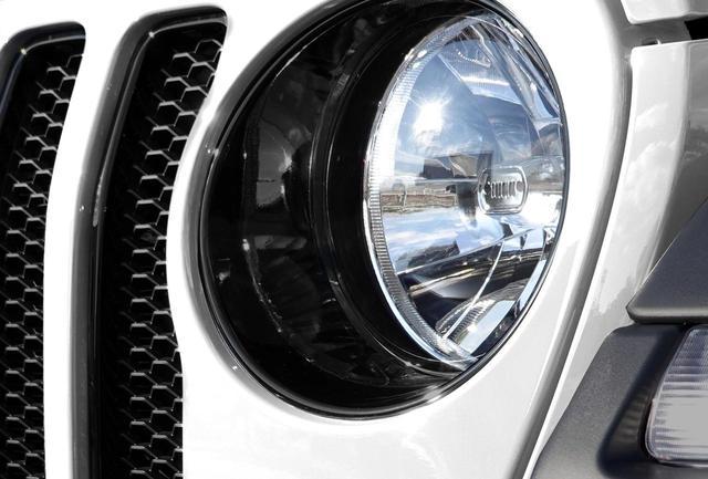 画像: ジープ ラングラー アンリミテッドスポーツ アルティチュードのヘッドライトとグリルのフチなどに、グロスブラック加工が施される。
