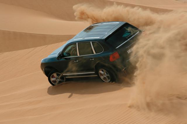 画像: 砂塵を巻き上げながらアラブの大地を走り抜けるカイエンターボS。緻密な駆動力制御で40偏平のオンロードタイヤでもトラクションを獲得できる。